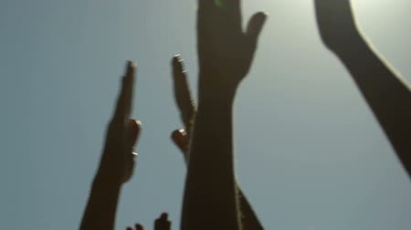 参加する : Pleased people raising and clapping hands at summer music festival, close-up