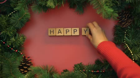 frase : Happy New Year, female hand making phrase of cubes on decorated background