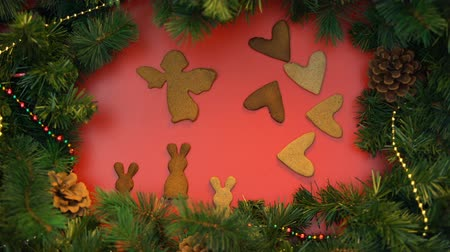 stopmotion : Gingerbread cookies dancing on decorated spruce branches background.