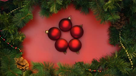newyear : Red christmas balls moving around decorating spruce branches, stop-motion