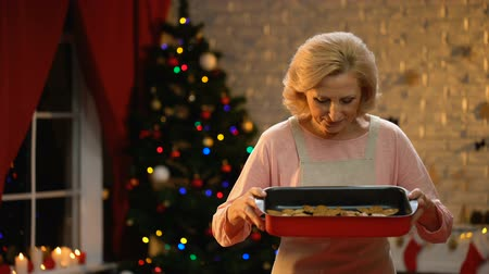 пенсионер : Lady smelling traditional Xmas cookies in dish, preparations before holiday