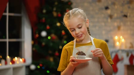 christmas tree with lights : Little happy girl holding plate with choco muffin, preparations before holiday