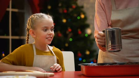 vdolky : Excited girl looking at granny powdering traditional Xmas muffins with sugar