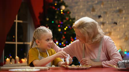 miraculous : Excited girl decorating Xmas cookies with granny, family festive traditions