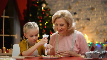 csőd : Retiree lady looking how excited girl decorates Xmas biscuits.