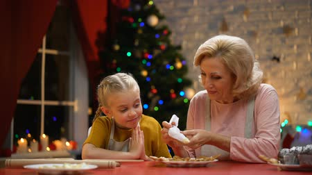 emeryt : Cheerful granny and girl decorating cookies for Christmas party, happy holidays