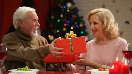 lasting : Happy elderly couple exchanging presents, long lasting marriage, Xmas eve
