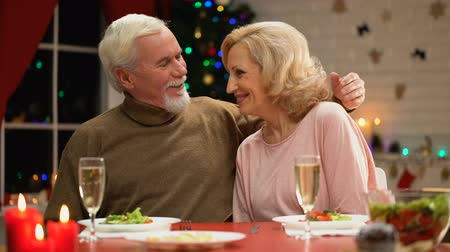szenteste : Retiree couple hugging and looking to camera, happy family portrait on Xmas eve