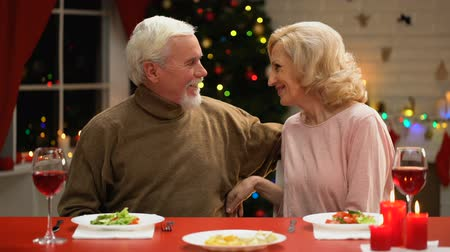 lasting : Aged couple celebrating Xmas tenderly kissing and hugging, long-lasting marriage