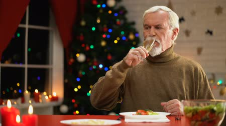 меланхолия : Lonely male sitting near sparkling Xmas tree having champagne on Christmas eve