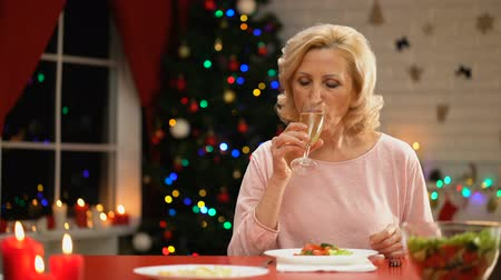 recordando : Lonely lady drinking champagne celebrating Christmas smiling to camera.