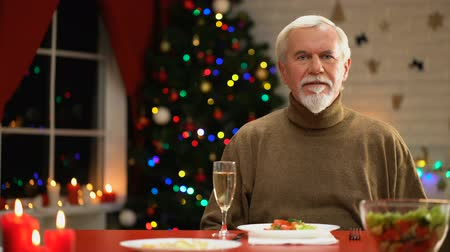 recordando : Sad man celebrating Xmas alone, looking to camera, social services for retirees Archivo de Video