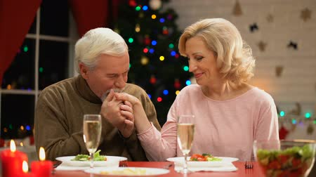 lasting : Aged man kissing lady hand tenderly, woman flirting, Christmas eve celebration