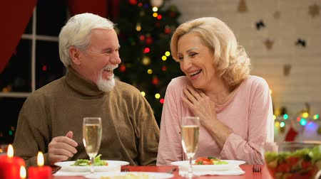 lasting : Happy aged couple smiling and laughing, having good time together on Xmas eve