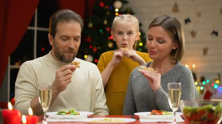 dilek : Cheerful family eating traditional Xmas cookies, looking to camera, traditions Stok Video