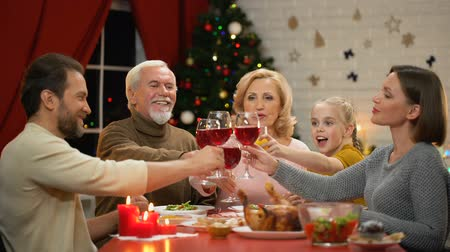 confortável : Big friendly family clinking glasses with wine on Xmas eve, looking to camera Vídeos