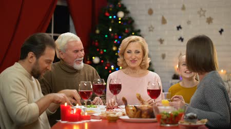 szenteste : Happy family having tasty healthy Xmas dinner together lights on tree glittering Stock mozgókép