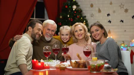 miraculous : Friendly family hugging and looking to camera, Xmas dinner, portrait effect
