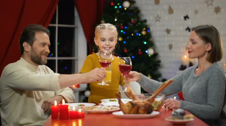 kinderwens : Mom and dad clinking wine on Xmas eve, girl drinking juice, looking to camera