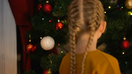 auguri : Lonely girl hanging ball on Christmas tree in orphanage, thinking about family