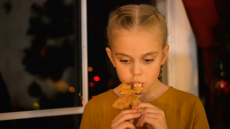 auguri : Sad girl eating Xmas cookie, standing near window, orphan charity organization