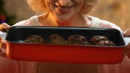 x mas : Old woman holding freshly baked cupcakes, holiday treats, Christmas traditions