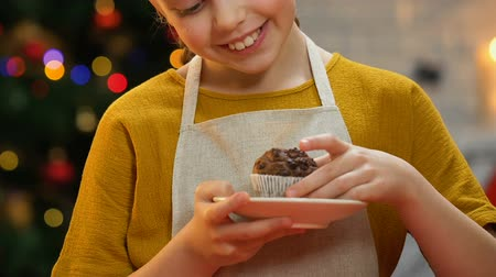 baked pudding : Girl in apron holding cupcake, smiling at camera, happy Christmas childhood