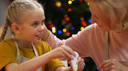 louvor : Little girl decorating gingerbread with icing sugar, granny hugs and praises kid Vídeos