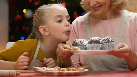 desobediente : Girl blowing sugar powder from cupcakes, laughing with granny, fun together