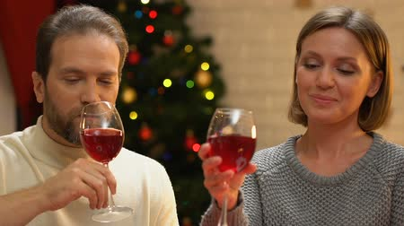 miraculous : Happy couple drinking wine and embracing, romantic date at Christmas, closeup Stock Footage