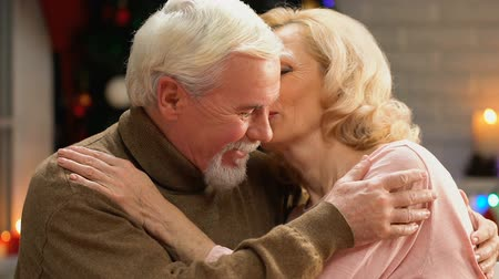 caring : Senior couple embracing lovingly, celebrating Christmas, happy together, closeup Stock Footage