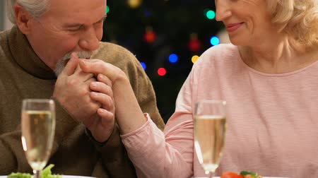 miraculous : Old gentleman kissing hand of beloved wife, romantic Christmas Eve dinner.