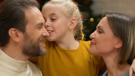 xマス : Girl kissing mom and dad on cheeks, showing love and care to family on Christmas