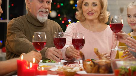 juntar : Family raising toast at Christmas dinner, tradition to get together for holidays