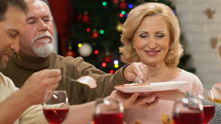 pozitivní : Family eating meat at holiday table, celebrating Christmas together, closeup