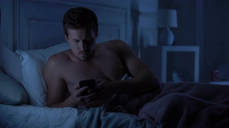 atmak : Handsome male lying in bed, reserving disappointing text message on smartphone