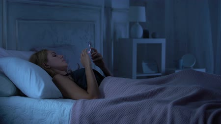 admirado : Lady in seductive lingerie lying in bed chatting on smartphone, boyfriend coming Stock Footage