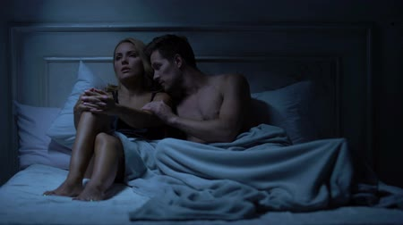 cheerless : Couple quarreling in bed, male trying to apologize, lady pushing him away Stock Footage
