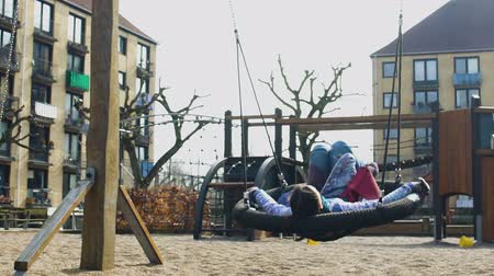 copenhagen : Female student relaxing in swing on city playground, freedom and inspiration
