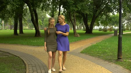 отпрыск : Mother and daughter walking along park chatting and laughing, pastime together Стоковые видеозаписи