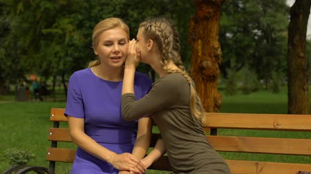 compreensão : Young daughter sharing secrets with mom, relaxing in park, trusting relationship