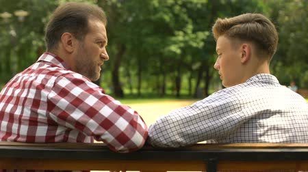 schoolkid : Teenage son talking with father on bench in park, dad supporting his child