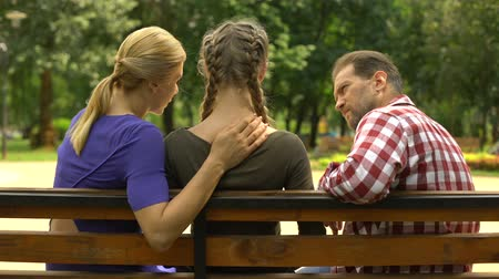período : Loving parents supporting depressed daughter sitting on bench in park, sadness Vídeos