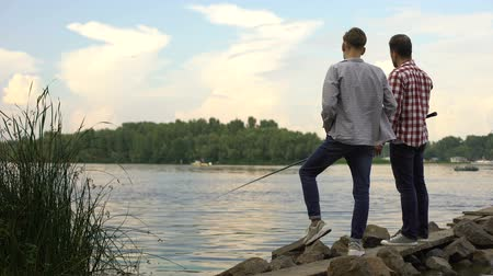 vader en zoon : Father and teenager son fishing together, relaxing near lake.