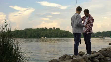 ryba : Father and 16 years old son preparing fishing rods, relaxing together near lake Dostupné videozáznamy
