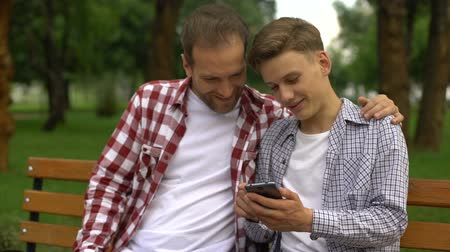 travessura : Male teenager and dad watching funny video on smartphone, laughing and smiling
