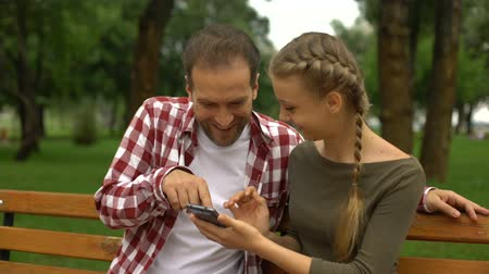 travessura : Cute teenage daughter showing funny video on cellphone to father, relax in park