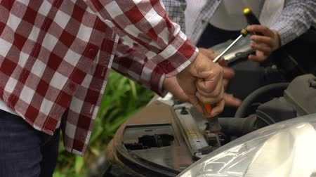 szerelő : Two male mechanics fixing car engine failure, vehicle maintenance service