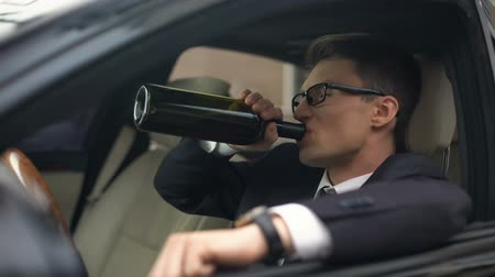 penas : Drunk businessman drinking wine in car, accident risk, rest after stressed job Stock Footage