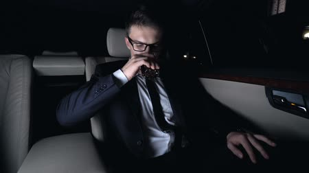 elite : Millionaire drinking glass of elite brandy on back seat of car, business trip
